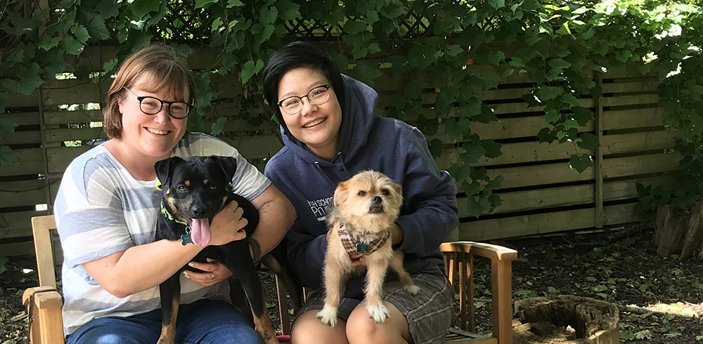 Natalie Kearns and Natalie Tsang sit outside with their dogs.